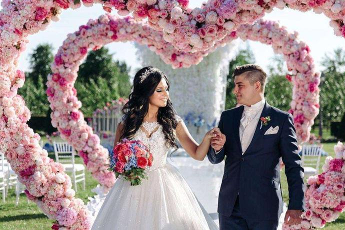 婚礼鲜花拱门是婚礼现场布置必不可少的一个关键装饰,整个婚礼的气质和婚礼的灵魂都是在入场拱门上,拱门有的是铁艺支架搭配布艺和鲜花制成,有的是纯天然的木制搭配大量花束支撑等等。